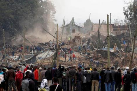 Residents looking helplessly as a bulldozer pulls down their houses.