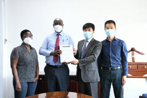 KeNHA Director General Peter Mundinia (second left) holds the signed tender award to China Communication Construction Company alongside the firm's officials