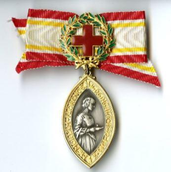 A Florence Nightingale Medal made with a ribbon with colours red, green and yellow on it. The medal is made of a metal.