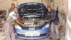 Mechanics working on a car in a Nairobi city garage.
