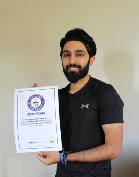 Alikan Kazia poses for a photo holding his Guinness World Record Certificate