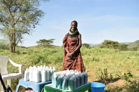 A Turkana lady standing beside a display of shampoo and liquid soap on sale.