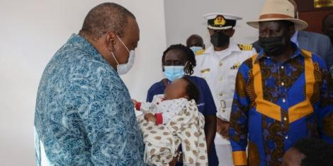 President Uhuru hold baby as they inspect NMS hospital with Raila in Kibra on September 29,2021