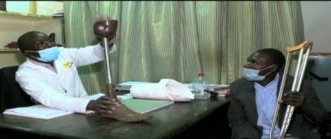 Name Stephen Chege Paying Attention to a Doctor Explaining To Him How His Prothetic Leg Would look Like
