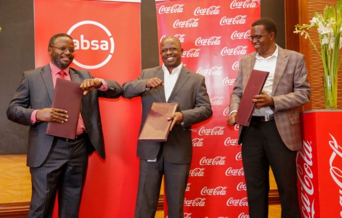 Coca-Cola Beverages Africa – Kenya Sales and Marketing Director, Josephat Mwangi (right) looks on as ABSA Regional Corporate and Investment Banking Director East Africa, James Agin (center) is being engaged by with Amref Health Africa Country Director – Kenya, Dr. Meshack Ndirangu (left) as they are holding an MOU between the three companies.