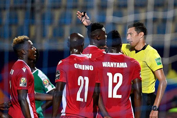 Egyptian referee Ghead Grisha (right) speaks to Kenyan players during their 2019 Africa Cup of Nations (CAN) Group C match against Senegal at the 30 June Stadium in the Egyptian capital Cairo on July 1, 2019.