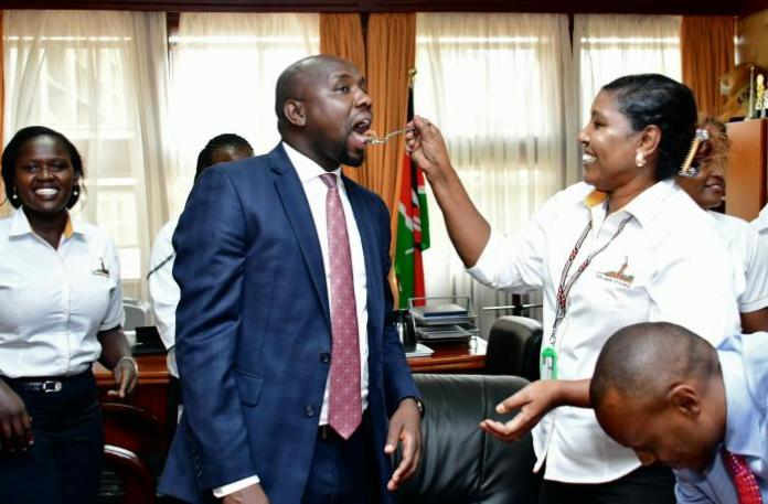 Photo of Kipchumba Murkomen receiving a cake from a member of his staff at his offices on March 12, 2020.