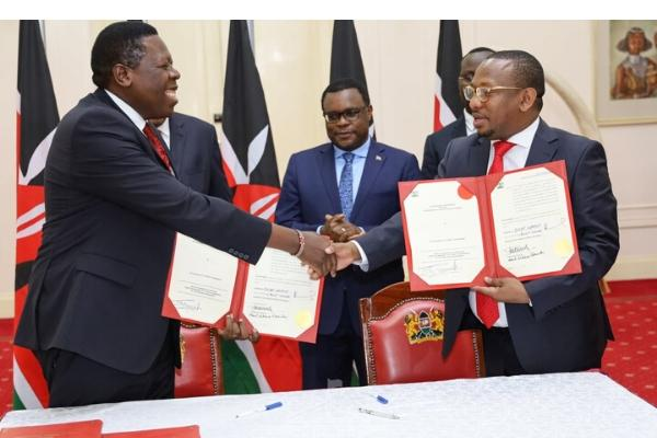 Devolution CS Eugene Wamalwa (left) and Nairobi County Governor Mike Sonko (left) shake hands after signing the deed of transfer of functions on Tuesday, February 25, 2020 at State House, Nairobi