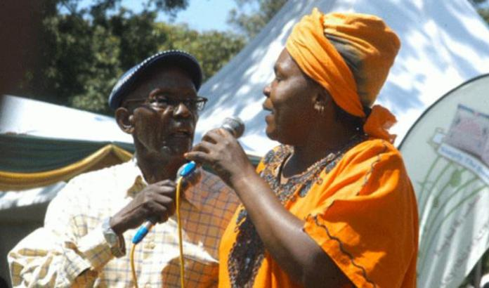 Benson Wanjau alias Mzee Ojwang Hatari (R) with Mary Khavere alias Mama Kayai acting at an event.