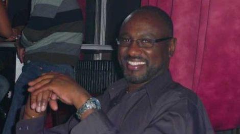 Robert Kirubi smiling as a picture is taken of him.