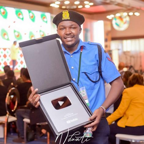 Comedian Alex Mathenge receiving an accolade from YouTube