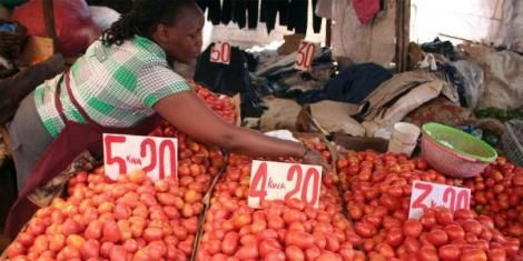 A woman selling tomatoes at a market in Kenya