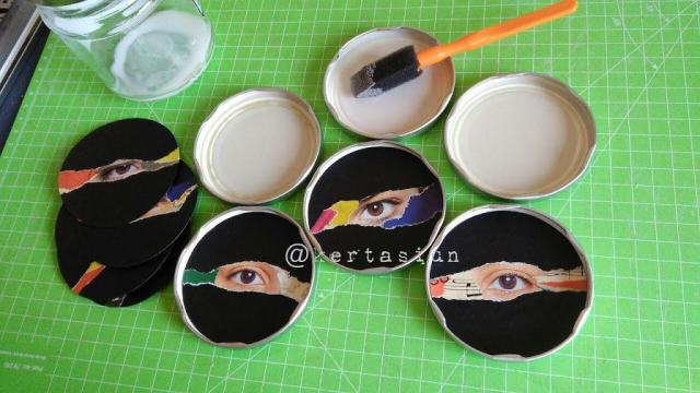 Working on progress of paper collage on metal jar lid with scrap images of eyes