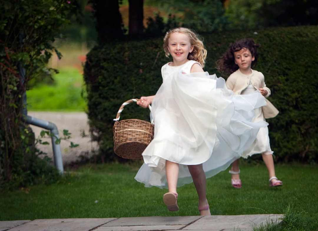Flower girls running and laughing with basket at Herefordshire wedding