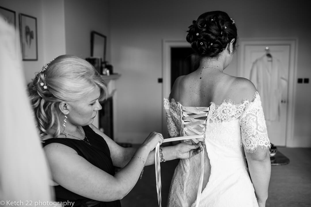 Bride having the back of her wedding dress laced up at bridal preparations
