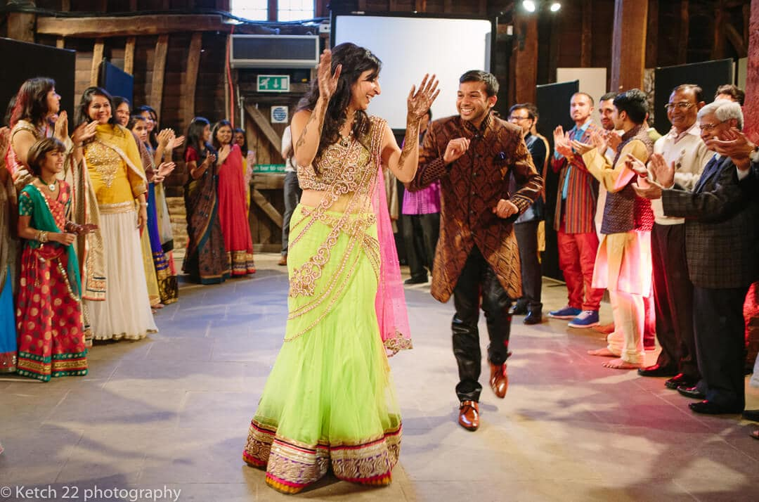 Bride in green and pink with groom dancing at Indian henna night in London