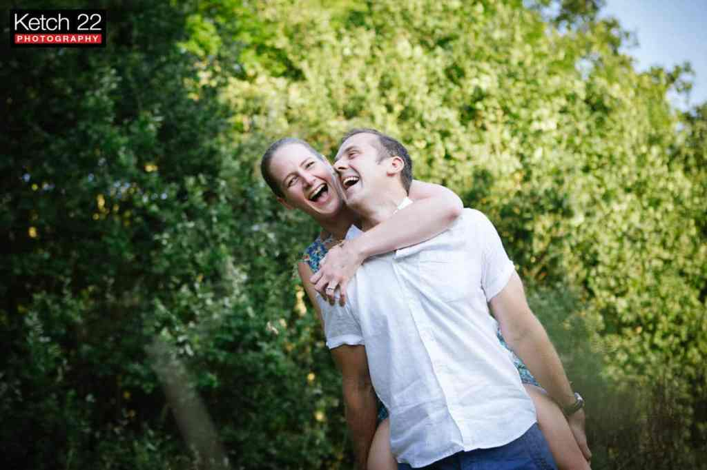 Happy engaged couple laughing at Woodchester Gloucestershire