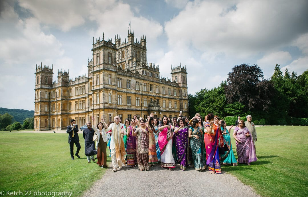 Wedding guests cheering in front of Highclere castle