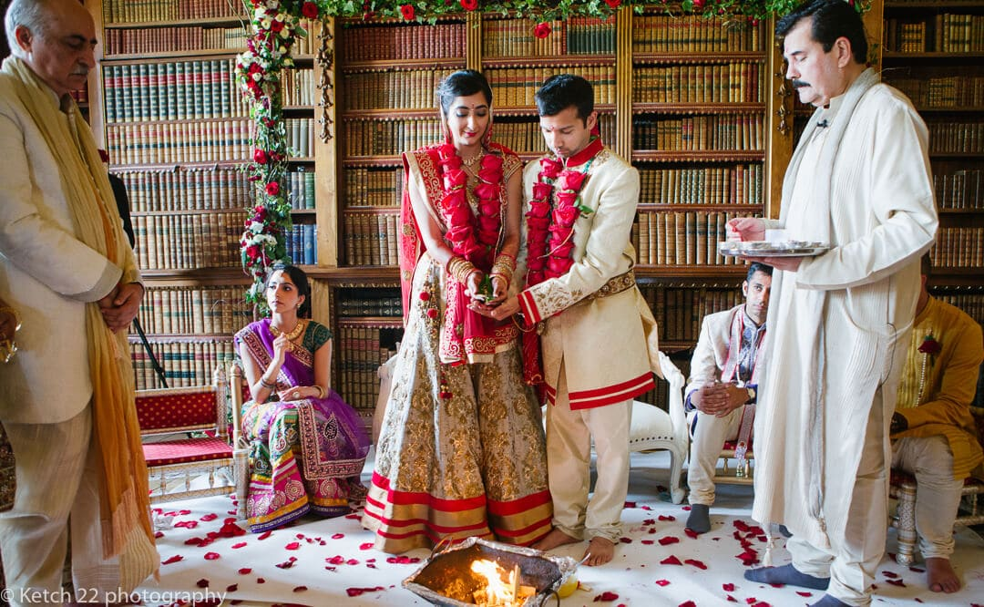 Bride and groom standing over fire at Indian wedding
