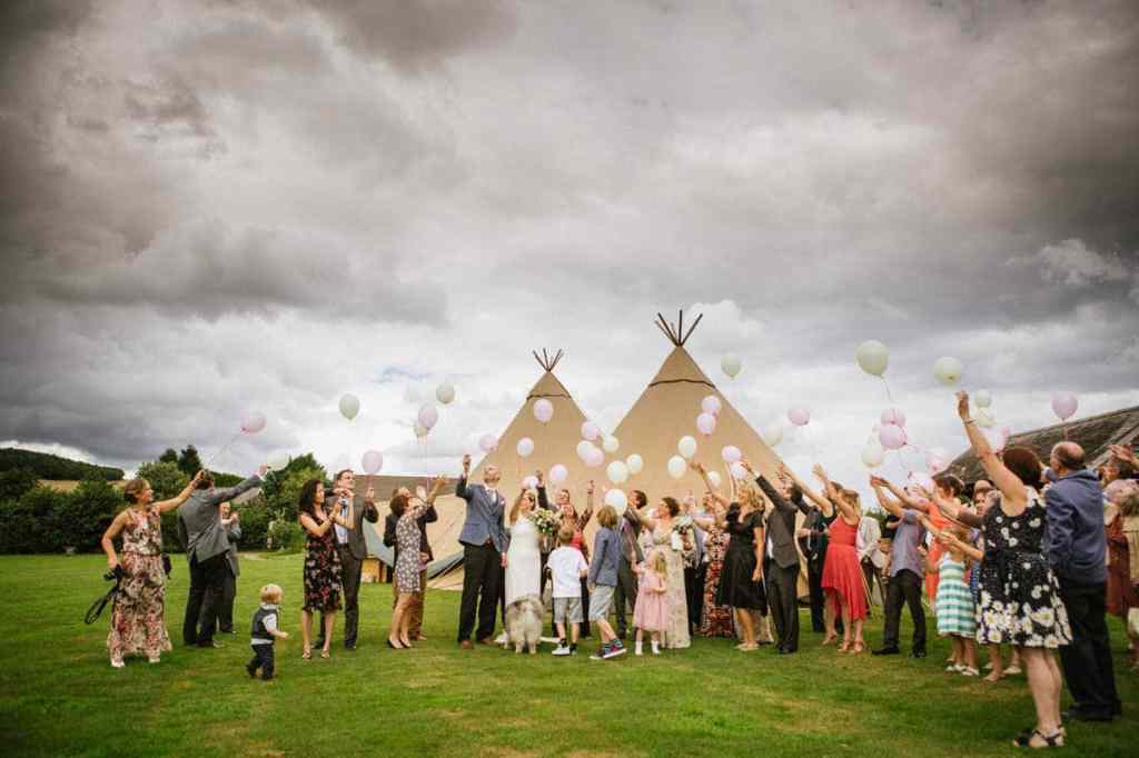 Wedding guests releasing balloons into the sky outside vintage marquee in Shropshire