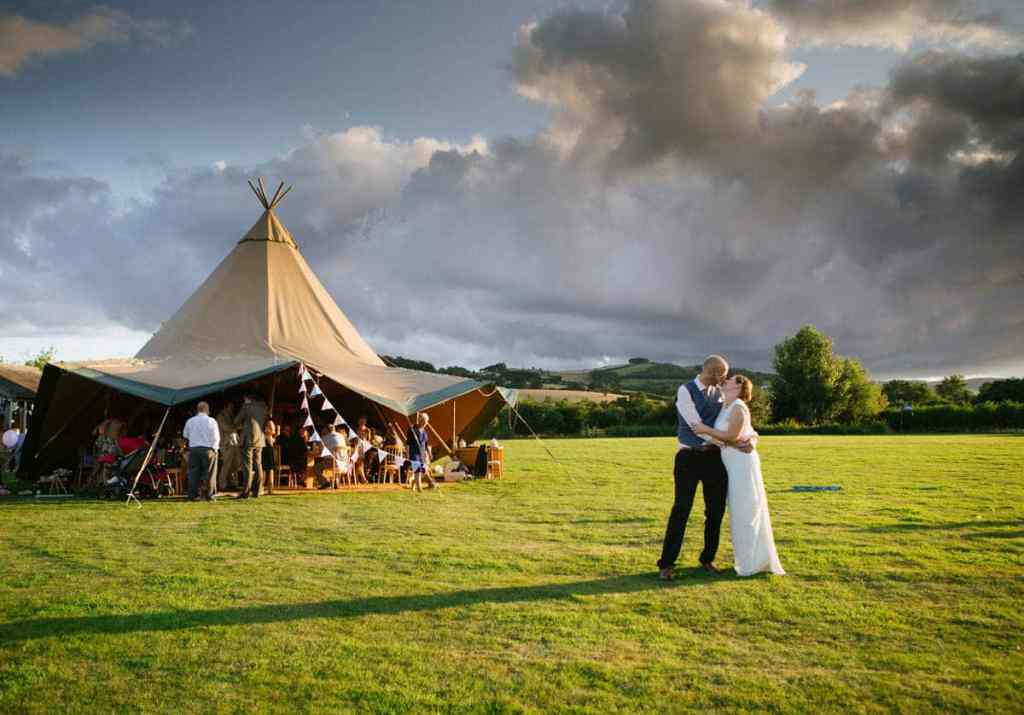 Bride and groom kissing in front of wigwam tent at wedding in Shropshire