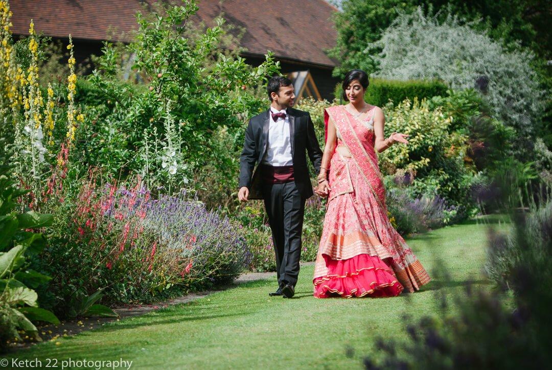 Hindu bride and groom walking through gardens at Micklefield Hall