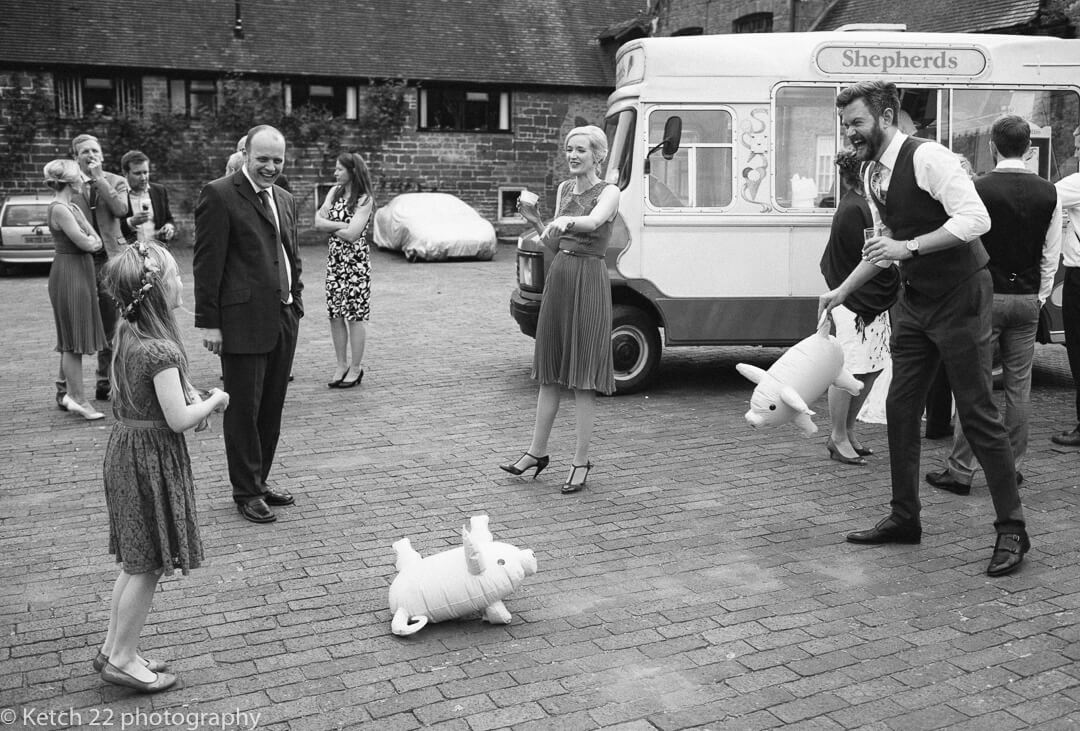 Wedding guests playing with inflatable pigs at How Caple Court in Herefordshire