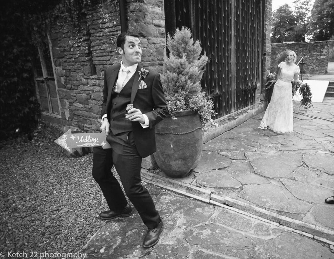 Groom making rude gestures with wedding sign at How Caple Court