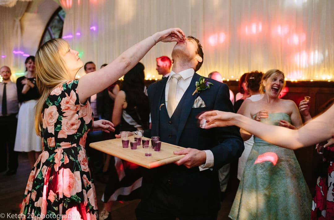 Groom knocking back shots at wedding reception