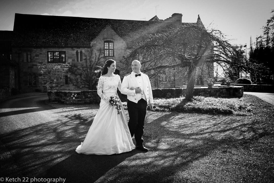 Bride and groom walking in front of Brinsop Court wedding venue