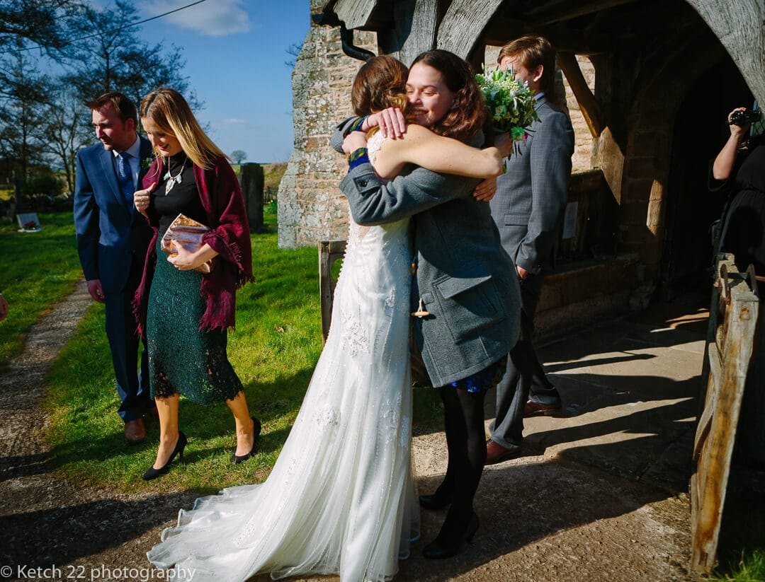 Bride hugging friend outside church at Herefordshire wedding