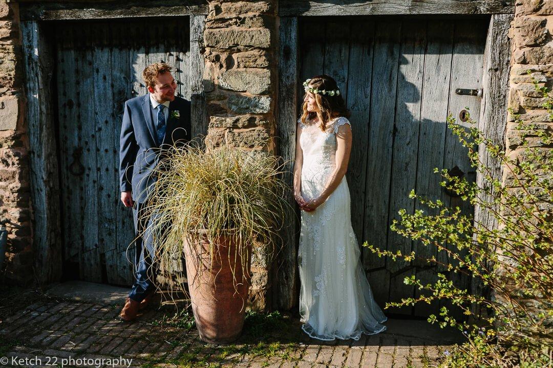 Portrait of bride and groom in front of rustic blue doors