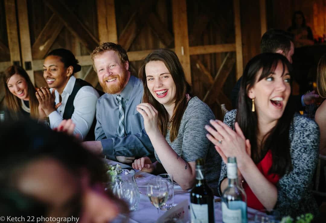 Wedding guests cheering at speeches at barn wedding
