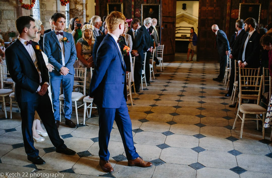 Groom waiting for bride to enter wedding ceremony room