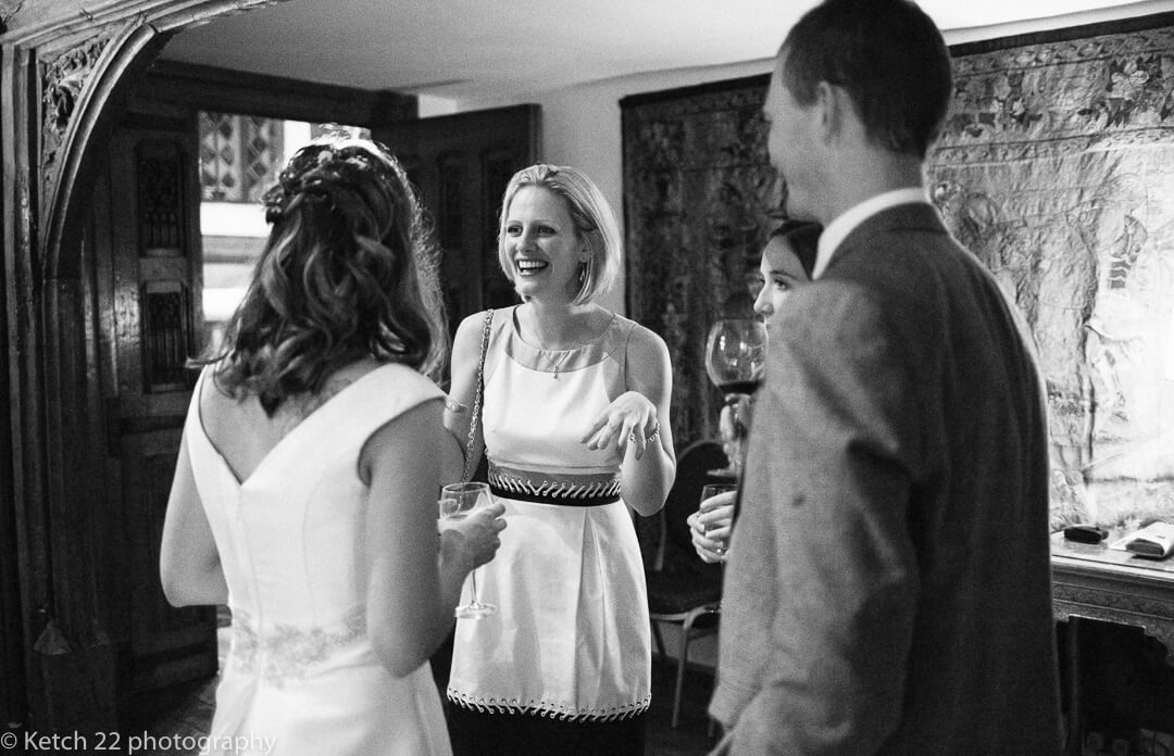 Wedding guest laughing and chatting to bride at reception