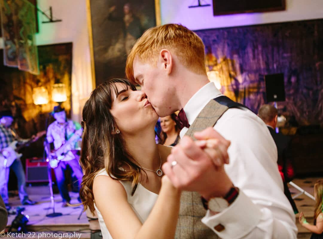 Candid photo of bride and groom kissing at wedding reception