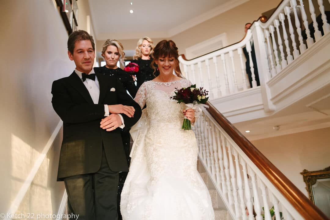 Bride descending stairs at Gloucestershire wedding