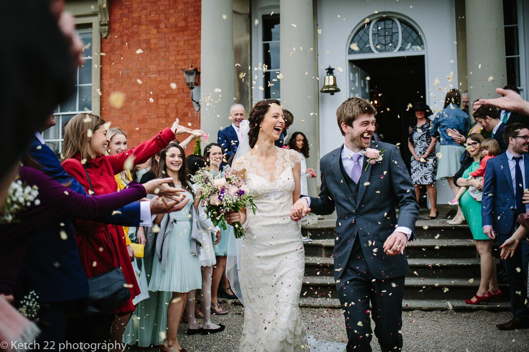 Colourful photo of bride and groom getting showered with confetti at recommended wedding venue Homme House