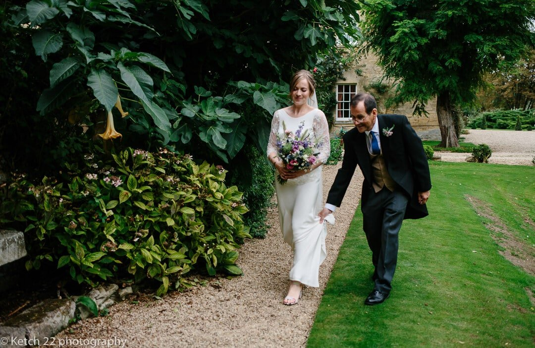 Bride with father walking through gardens at Upper Court wedding