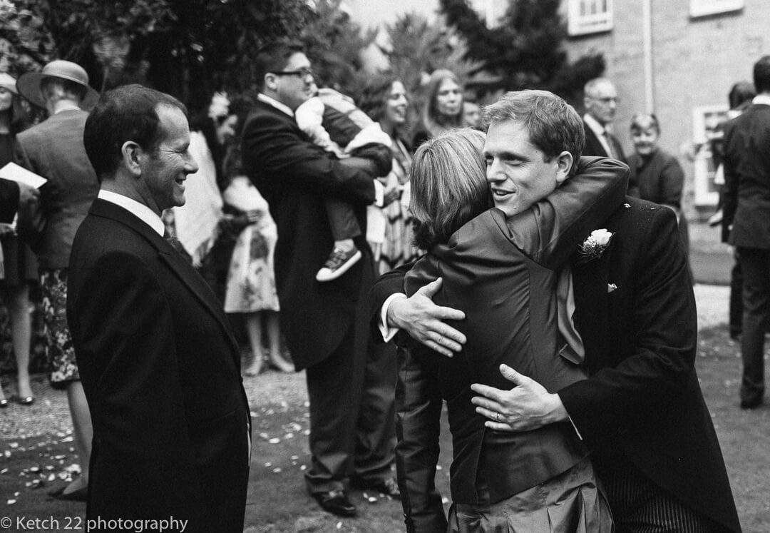 Groom hugging wedding guest