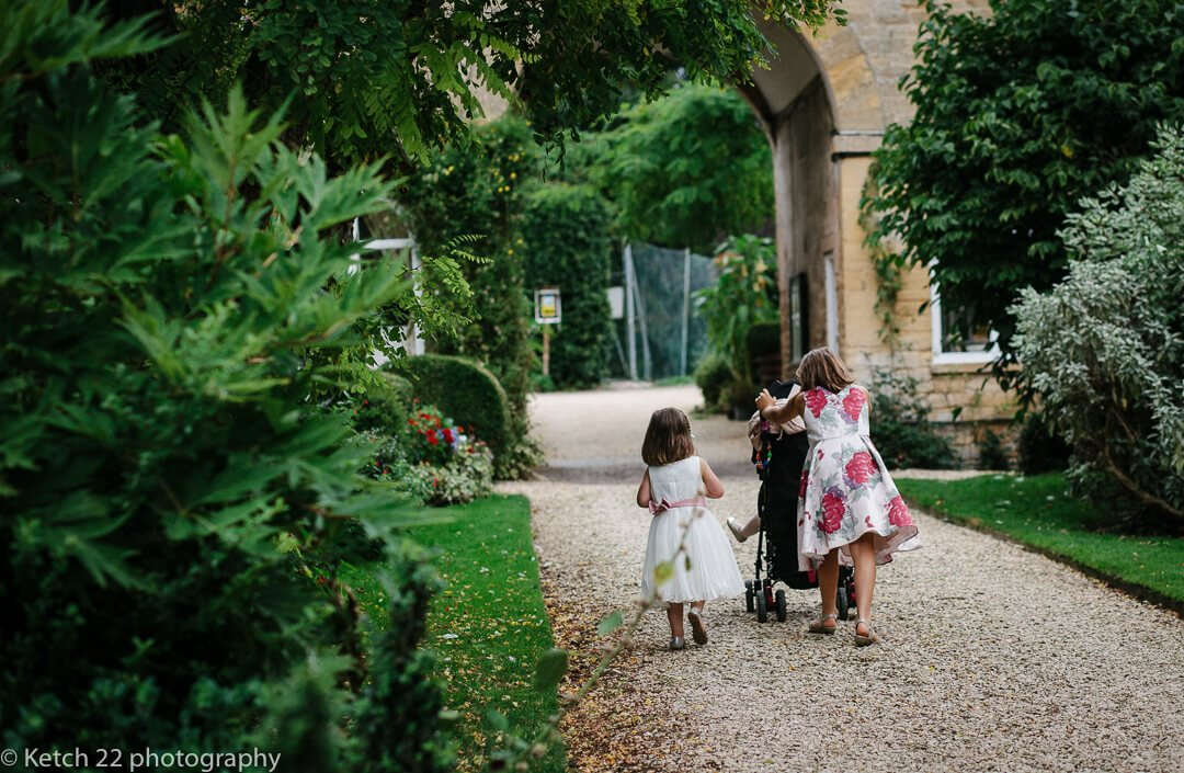 Kids pushing pram at country house wedding