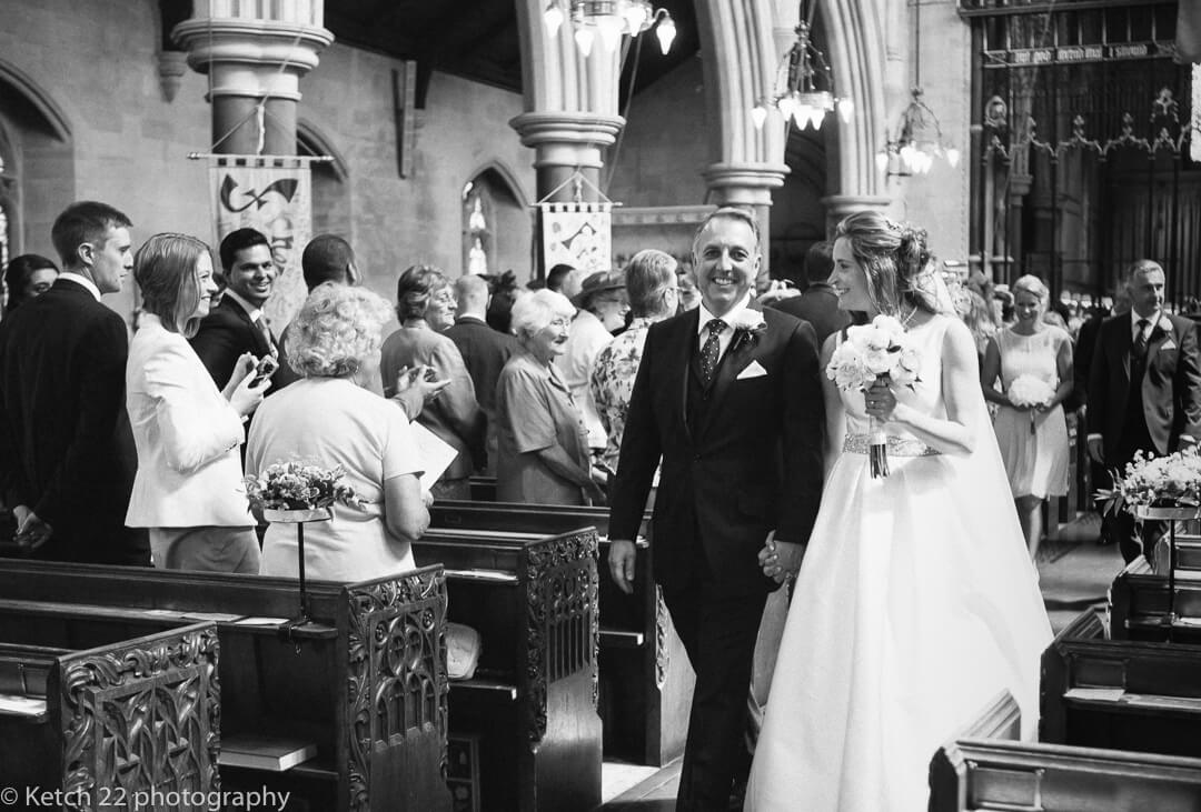 Newly weds leaving church with wedding guests looking on
