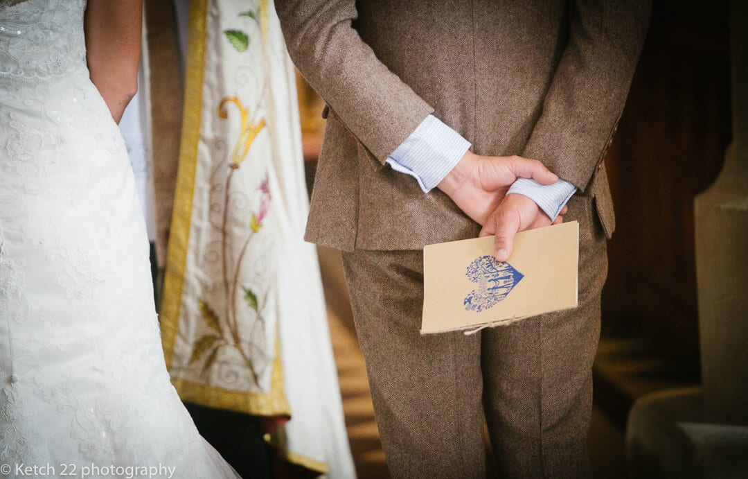 Groom holding order of service at wedding