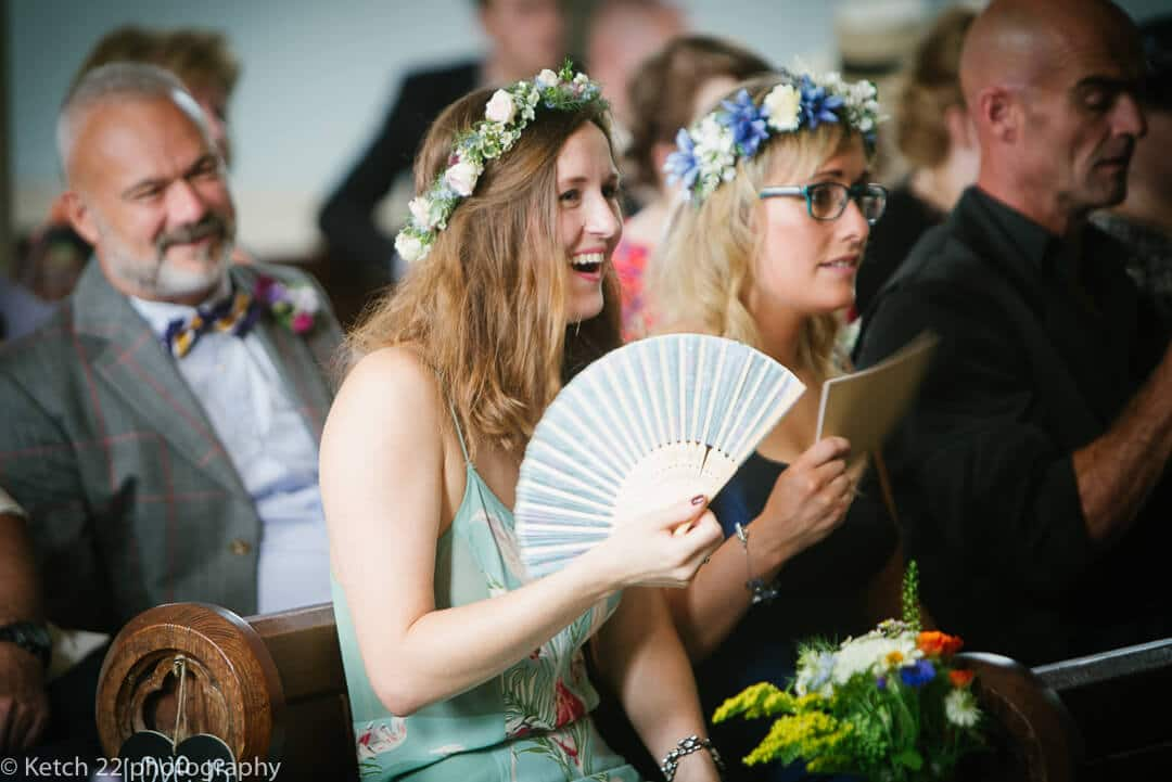 Bridemaids keeping cool with fans at hot summer wedding