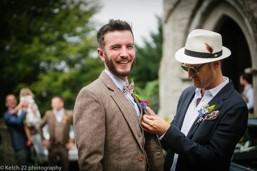 Best man buttons flower on grooms jacket at rural wedding