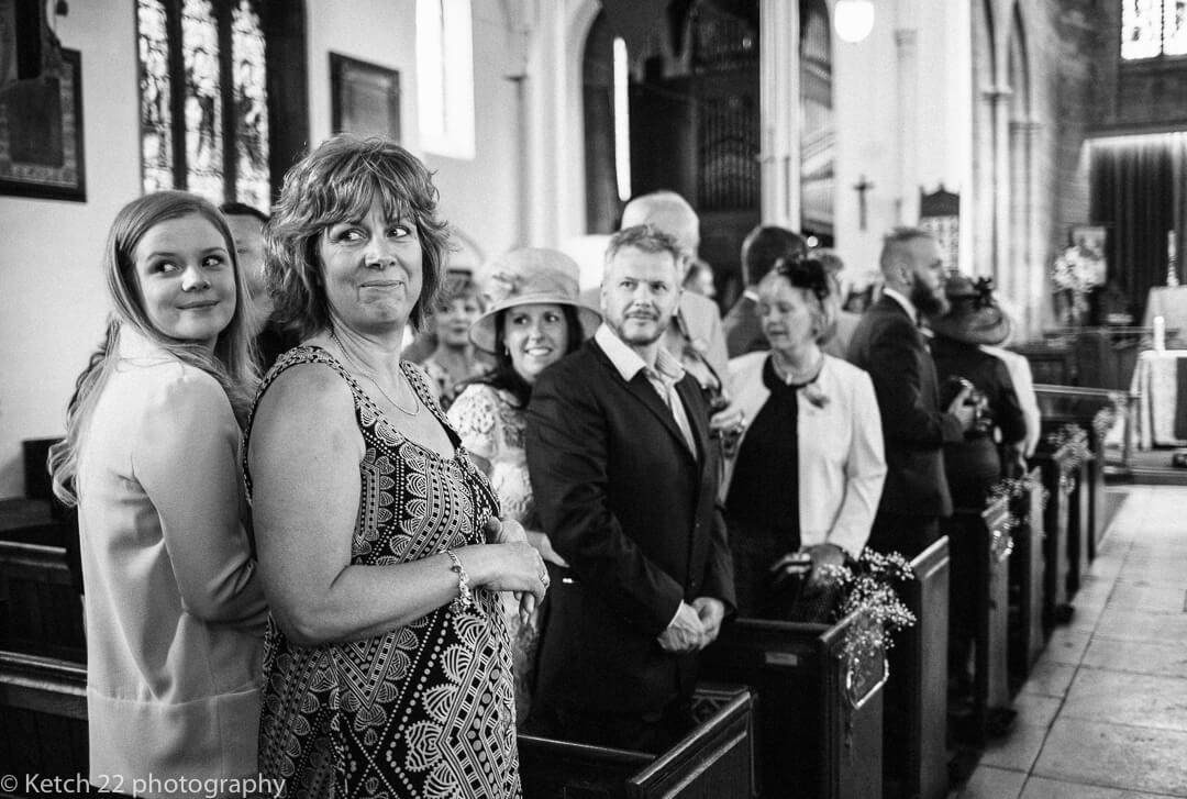 Wedding guests looking at bride enter church