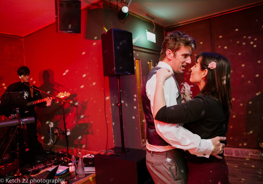Wedding guests dancing at reception in red light