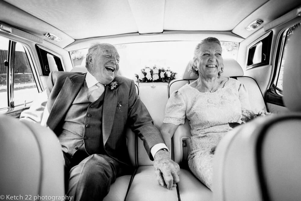 Never too late for love with older newly weddings laughing in car Gloucestershire