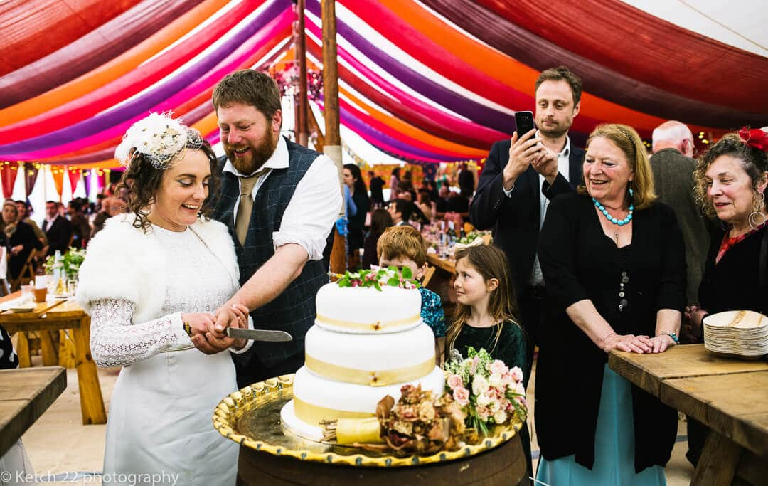 Bride and groom cutting cake with wedding guests looking on