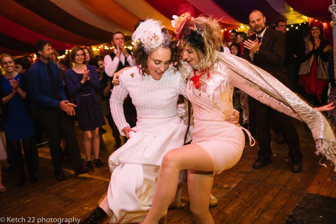 Bride dancing with friend at wedding reception